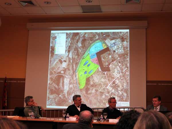 """Tres de los ponentes del debate """"Y de Ikea qué"""" con un mapa de la zona de Rabassa donde iría el macroproyecto proyectado en la pantalla durante el acto de la PIC"""
